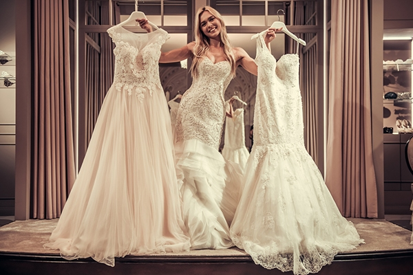 A bride to be chooses between two wedding gowns
