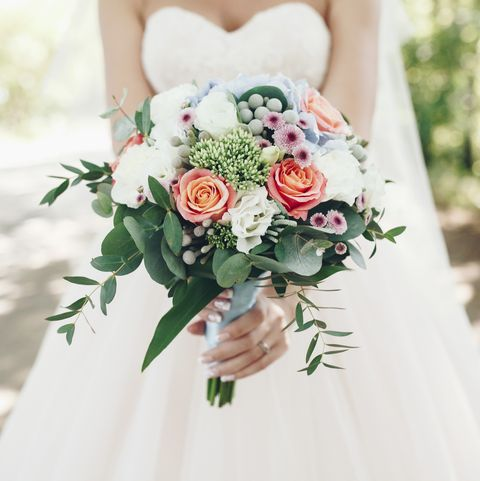 caucasian bride holding bouquet of flowers outdoors royalty free image
